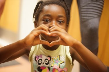 young girl making heart symbol with hands